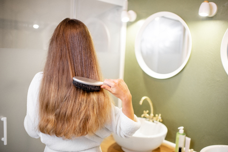Foto de Woman in bathrobe combing hair with brush in the bathroom, rear view - Imagen libre de derechos