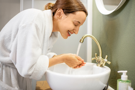 Photo for Woman in bathrobe washing her face from the facial mask in the bathroom - Royalty Free Image