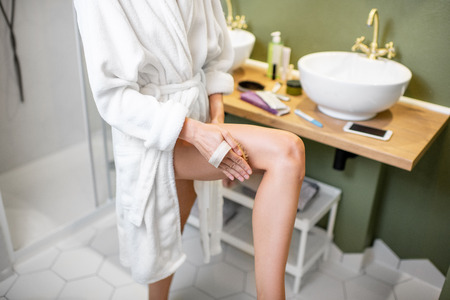 Photo pour Woman scrubbing her legs with a brush making skin peeling in the bathroom - image libre de droit