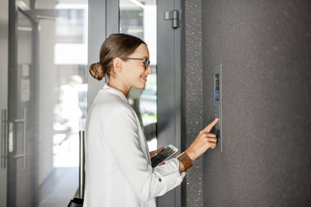 Photo for Young business woman in white suit entering code on the intercom keyboard of the residential modern building - Royalty Free Image