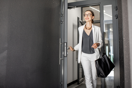 Photo for Young business woman in white suit going out of the residential building hurrying to work - Royalty Free Image