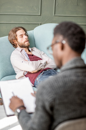 Foto de Young caucasian man visiting an african psychologist lying on the comfortable couch during psychological session in the green office - Imagen libre de derechos