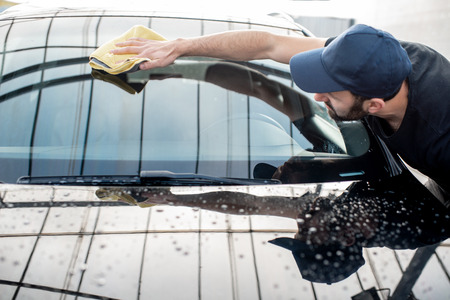 Foto de Professional washer in t-shirt and cap wiping windshield with yellow microfiber at the open air car wash - Imagen libre de derechos
