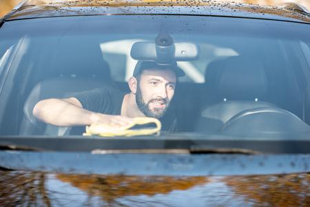 Foto de Professional washer wiping car panels with yellow microfiber, view through the windshield - Imagen libre de derechos