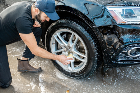 Foto de Professional washer in black uniform and cap wiping with sponge car wheel during the washing process outdoors - Imagen libre de derechos