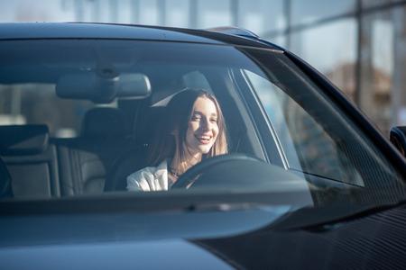 Foto de Young businesswoman driving a luxury car, view from the outside through the windshield - Imagen libre de derechos