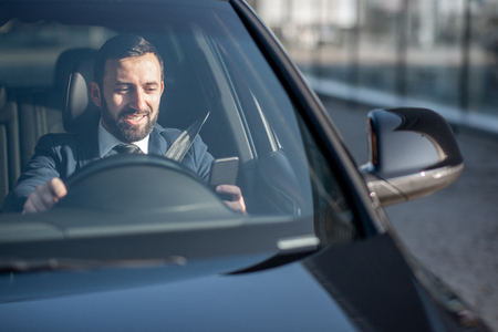 Foto de Happy businessman driving a luxury car, view from the outside through the windshield - Imagen libre de derechos