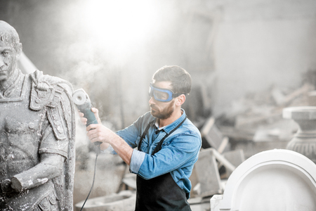 Foto de Sculptor in protective workware grinding stone sculpture with electirc grinder in the old studio with dust - Imagen libre de derechos