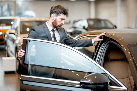 Photo pour Elegant businessman choosing new luxury car looking at the car intreior in the showroom - image libre de droit