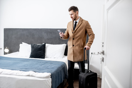 Foto de Dressed businessman standing with a suitcase and calling phone in the hotel room before the check out - Imagen libre de derechos
