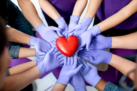 Foto de Group of people holding with hands in medical gloves red heart model. Close-up view. Healthy heart concept. - Imagen libre de derechos