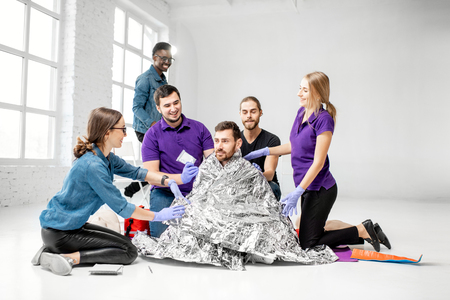 Photo pour People during the first aid training with instructors and man as injured person covered in thermal blanket indoors - image libre de droit
