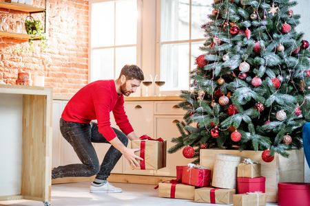 Foto de Man putting gifts under the Christmas tree preparing for a New Year holidays at home - Imagen libre de derechos