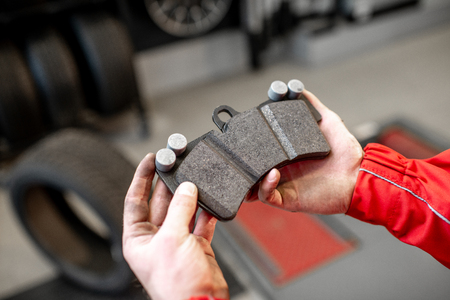 Foto de Auto mechanic holding new brake pad at the car service, close-up view - Imagen libre de derechos