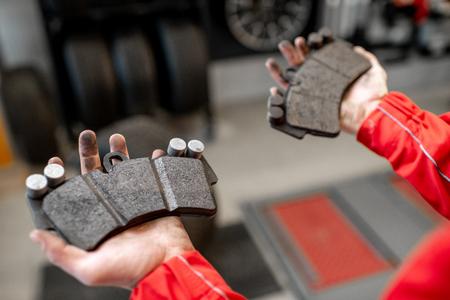 Foto de Auto mechanic holding new and used brake pads at the car service, close-up view - Imagen libre de derechos