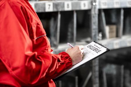 Photo pour Worker filling some documents in the warehouse, close-up view - image libre de droit
