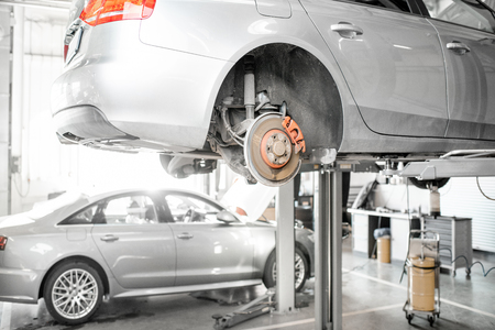 Photo pour Car standing on the hoist during the diagnostics at the car service - image libre de droit