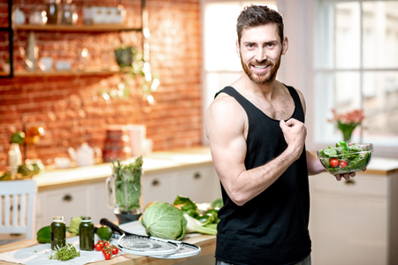 Photo pour Portrait of a handsome sports man showing muscles, eating healthy vegetarian salad on the kitchen at home - image libre de droit