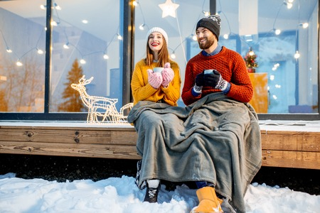 Photo for Young couple warming up with plaid and hot drinks sitting on the terrace of the modern house in the mountains durnig the winter holidays - Royalty Free Image