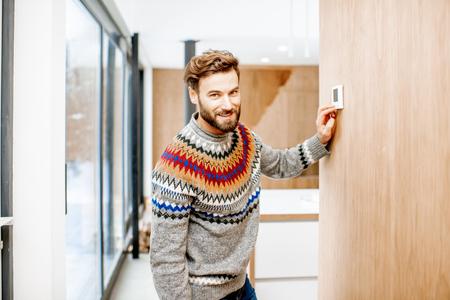 Foto de Man in sweater adjusting room temperature with electronic thermostat at home - Imagen libre de derechos