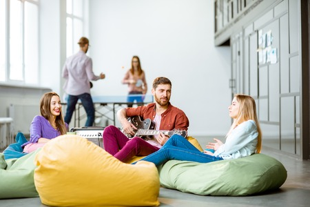 Photo for Group of a young coworkers having fun playing guitar and playing small tennis during the coffee break in the office - Royalty Free Image