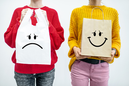 Photo pour Women holding plastic and paper bags standing on the white background. Ecological in contrast to non recyclable packaging concept - image libre de droit