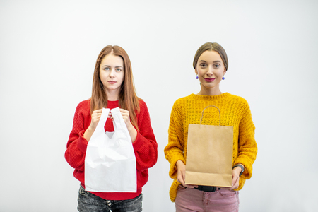 Photo for Portrait of a two women holding plastic and paper bags standing on the white background. Ecological in contrast to non recyclable packaging concept - Royalty Free Image