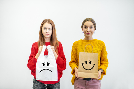 Photo pour Portrait of a two women holding plastic and paper bags standing on the white background. Ecological in contrast to non recyclable packaging concept - image libre de droit