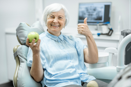 Photo pour Portrait of a beautiful senior woman with healthy smile holding green apple at the dental office - image libre de droit