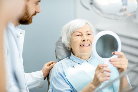 Foto de Happy elderly woman enjoying her beautiful toothy smile looking to the mirror in the dental office - Imagen libre de derechos