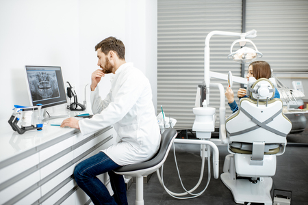 Photo for Dentist working with computer in the dental office with woman patient on the background - Royalty Free Image