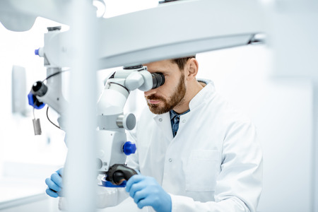 Photo for Male dentist examining patient looking on the teeth with professional microscope at surgery dental office - Royalty Free Image