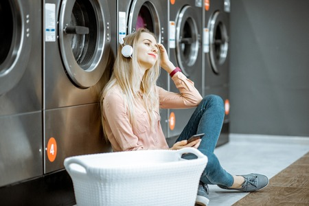 Foto de Young woman waiting for the clothes to be washed sitting on the floor and listening to the music at the self-service laundry - Imagen libre de derechos