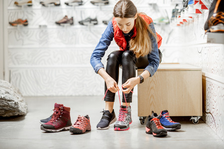 Foto de Woman trying shoes for mountain hiking sitting in the fitting room of the modern sports shop - Imagen libre de derechos