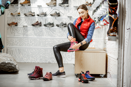 Photo for Woman trying shoes for mountain hiking sitting in the fitting room of the modern sports shop - Royalty Free Image