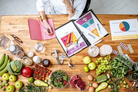 Photo pour Dietitian writing diet plan, view from above on the table with different healthy products and drawings on the topic of healthy eating - image libre de droit