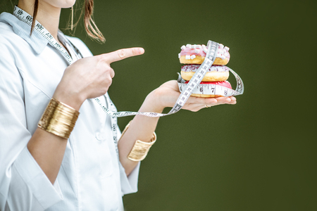 Photo for Woman showing on the sweet donuts on the green background. Unhealthy eating and adiposity concept - Royalty Free Image