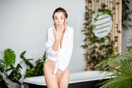 Foto de Portrait of a young seductive woman in white shirt in the beautiful bathroom with green plants. Womans beauty and sexuality concept - Imagen libre de derechos