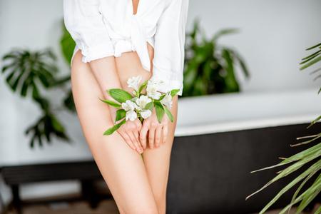 Foto de Beautiful womans body with flower covering her intimate place in the bathroom - Imagen libre de derechos