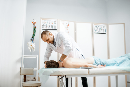 Photo pour Professional senior physiotherapist doing manual treatment to a mans cervical spine in the cabinet of rehabilitation clinic - image libre de droit