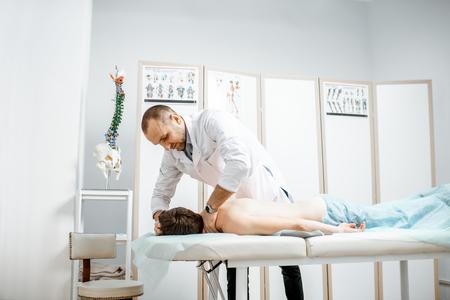 Foto de Professional senior physiotherapist doing manual treatment to a mans cervical spine in the cabinet of rehabilitation clinic - Imagen libre de derechos