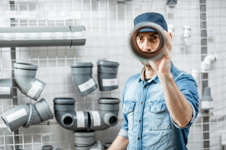 Photo pour Funny portrait of a handsome workman choosing sewer pipes standing near the showcase of the plumbing shop - image libre de droit