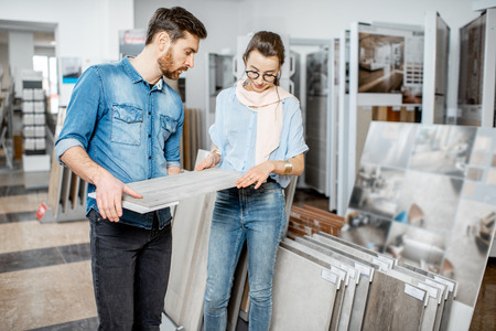 Photo pour Beautiful young couple choosing ceramic tiles for their house repairment in the building shop - image libre de droit