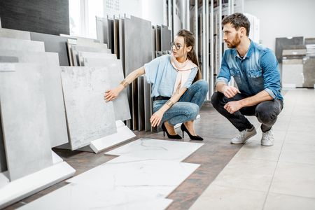 Foto de Beautiful young couple choosing big granite tiles for their house repairment in the building shop - Imagen libre de derechos