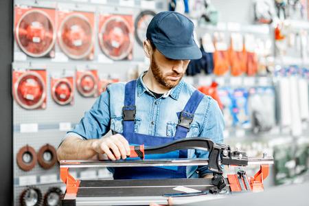 Foto für Handsome workman in uniform choosing professional tile cutter in the building shop - Lizenzfreies Bild