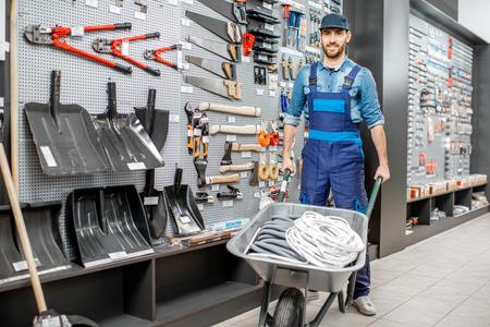 Foto de Portrait of a handsome worker in uniform standing with pushcart near the showcase with garden equipment in the shop - Imagen libre de derechos
