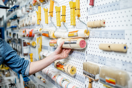Foto für Workman choosing tools for painting in the building shop, close-up view - Lizenzfreies Bild
