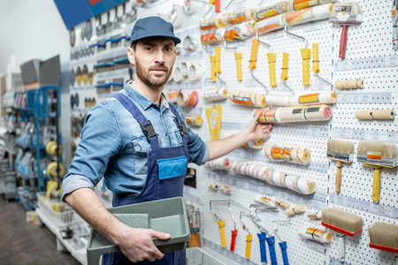Photo pour Handsome workman in uniform choosing tools for painting in the building shop - image libre de droit