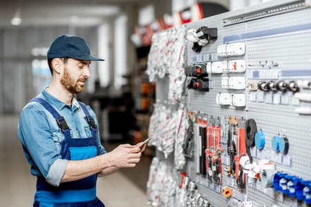 Photo pour Handsome electrician in workwear choosing electrical goods standing with smart phone in the building shop - image libre de droit
