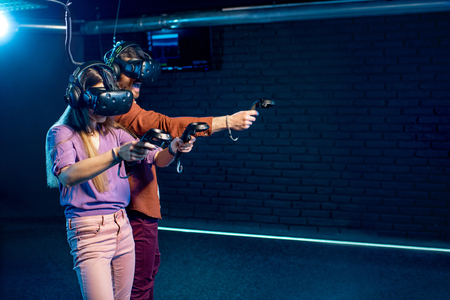 Photo pour Man and woman playing game using virtual reality headset and gamepads in the dark room of the playing club - image libre de droit
